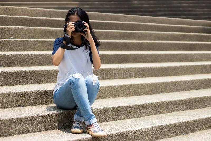 Den asiatiska flickan tar fotoet i stad arkivfoto