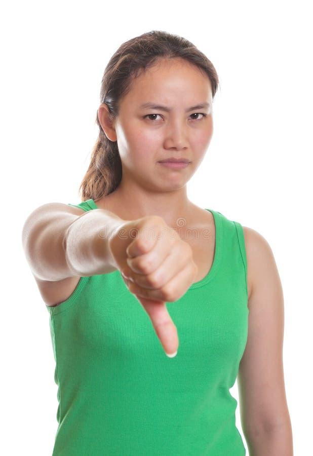 Den asiatiska flickan visar hennes tumme ner royaltyfri fotografi