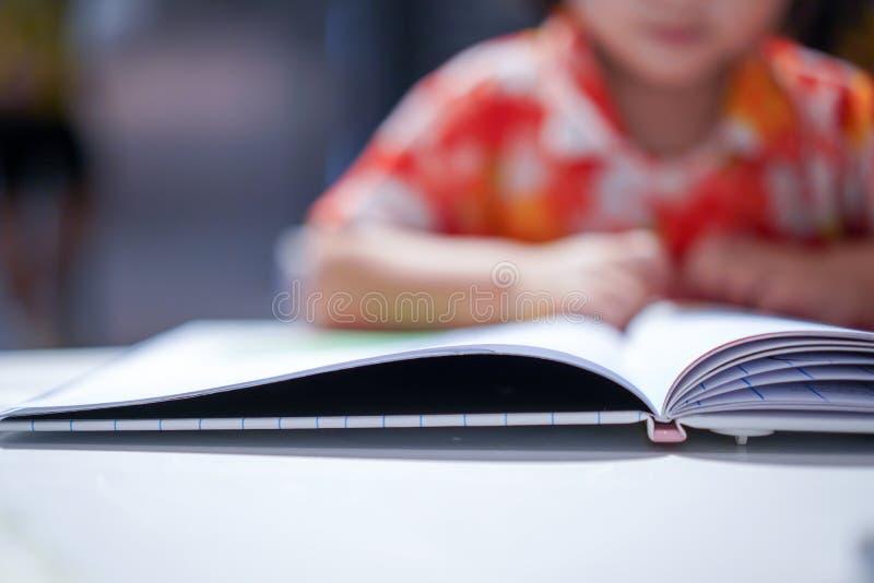 Den asiatiska flickaungen som koncentreras f?r att l?sa en bok, st?nger sig upp p? boken royaltyfria foton