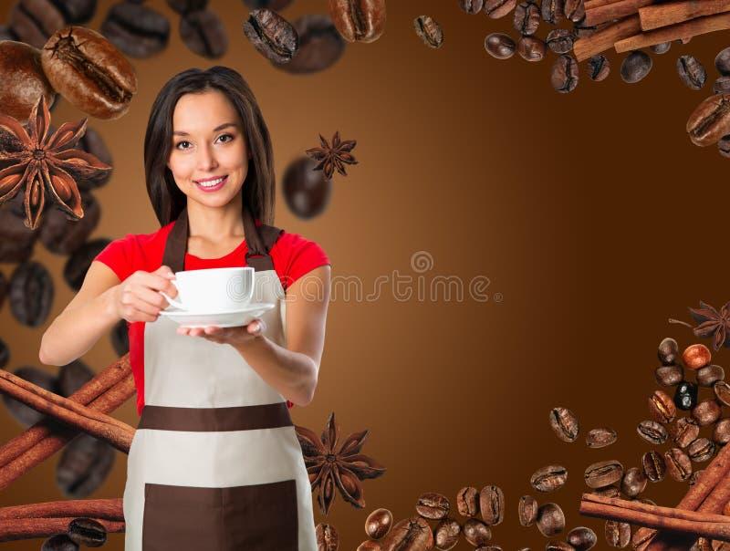 den asiatiska fokusen för koppen för bakgrundsbaristakaffe isolerade servingen som visar den le servitrisen vitt kvinnabarn Ungt  fotografering för bildbyråer