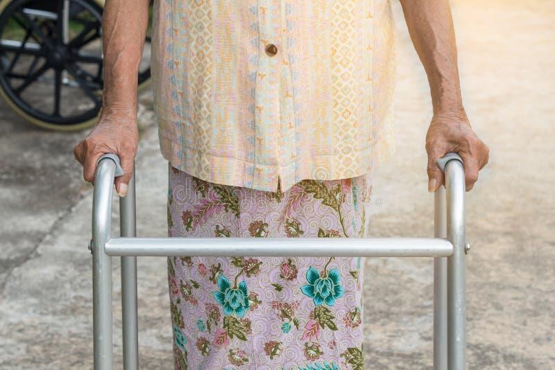 Den asiatiska gamla kvinnan som står med hans händer på en gå pinne, hand av den gamla kvinnan som rymmer en personalrotting med  royaltyfri bild