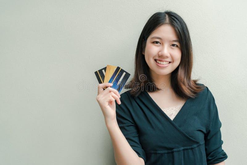 Den asiatiska härliga kvinnan som bär en svart skjorta, har en kreditkort i lyckligt framsidaanseende för hand i den gråa väggen arkivfoto