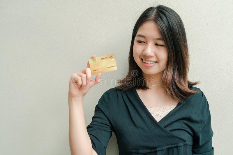 Den asiatiska härliga kvinnan som bär en svart skjorta, har en kreditkort i lyckligt framsidaanseende för hand i den gråa väggen royaltyfri fotografi