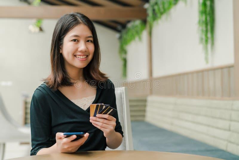 Den asiatiska härliga kvinnan som bär en svart skjorta som sitter i huset där, är en kreditkort i din hand, och du rymmer telefon arkivbild