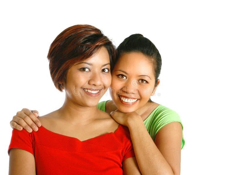 den asiatiska härliga kvinnlign ler två fotografering för bildbyråer