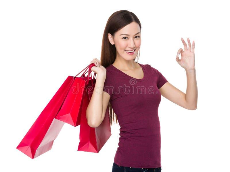 Den asiatiska hållen för den unga kvinnan med shoppingpåsen och det ok tecknet gör en gest fotografering för bildbyråer