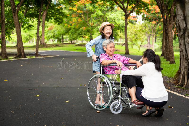 Den asiatiska höga kvinnan i rullstol med flickan för det lilla barnet som stöttar, tycker om på att gå den gröna naturen, farmor royaltyfri bild