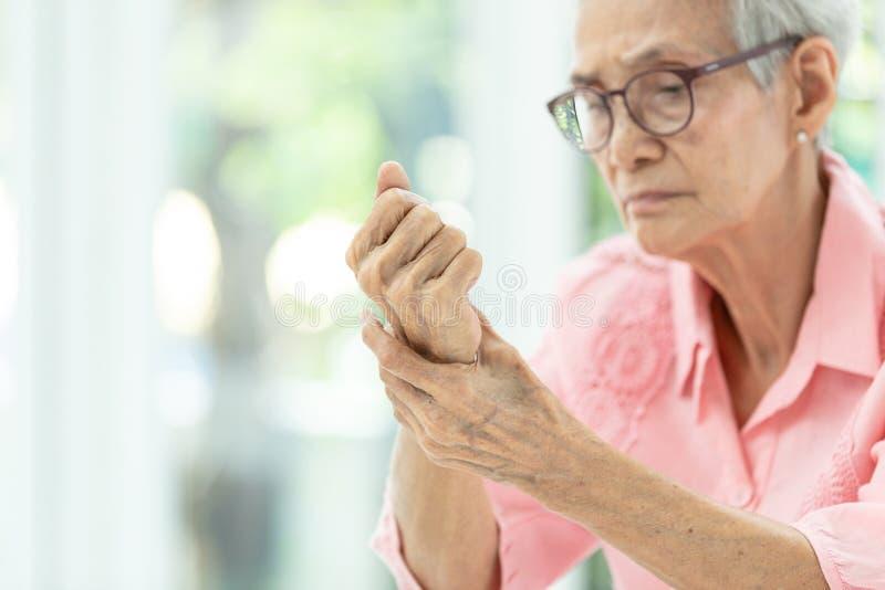 Den asiatiska h?ga kvinnan masserar hennes handleder, den ?ldre kvinnan som lider fr?n, sm?rtar i hand, artrit, beriberi eller pe arkivfoton