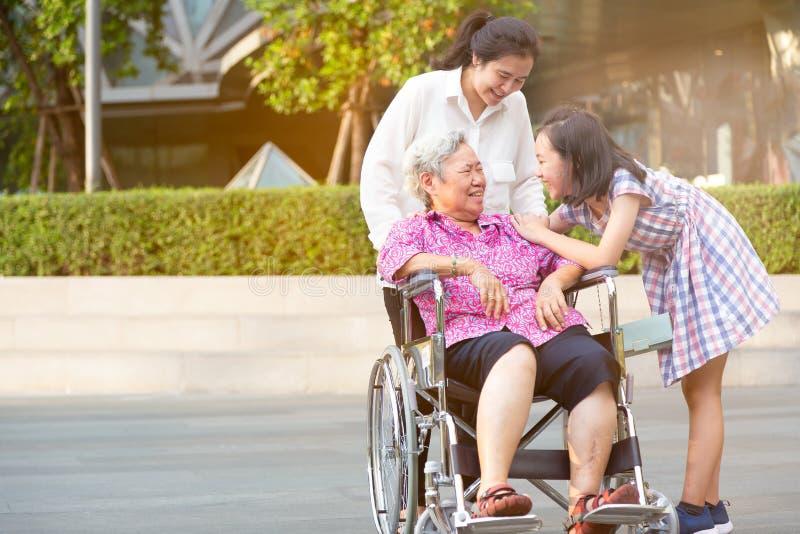 Den asiatiska höga kvinnan som har lycka och ler med hennes dotter, och sondottern på rullstolen på utomhus- parkerar, den äldre  royaltyfri foto