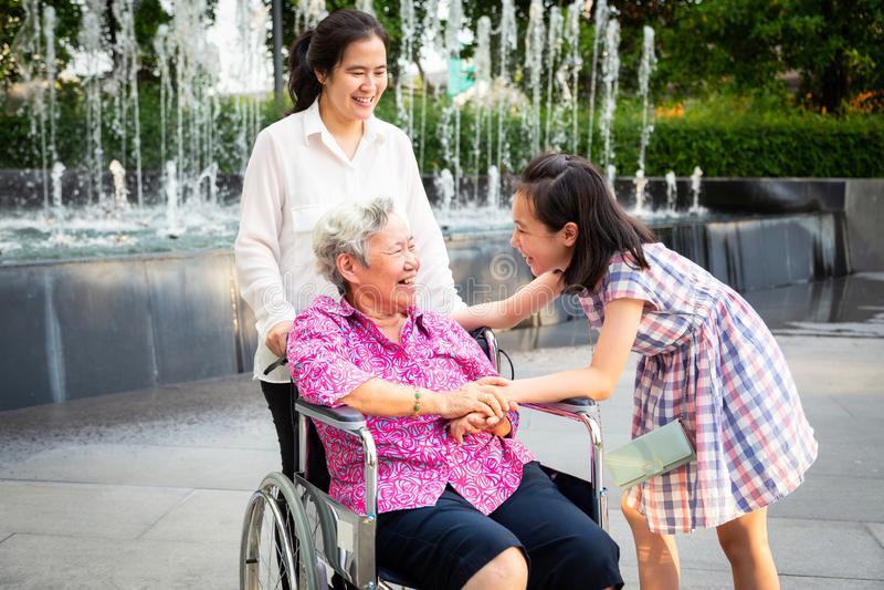 Den asiatiska höga kvinnan som har lycka och ler med hennes dotter, och sondottern på rullstolen på utomhus- parkerar, den äldre  royaltyfri fotografi