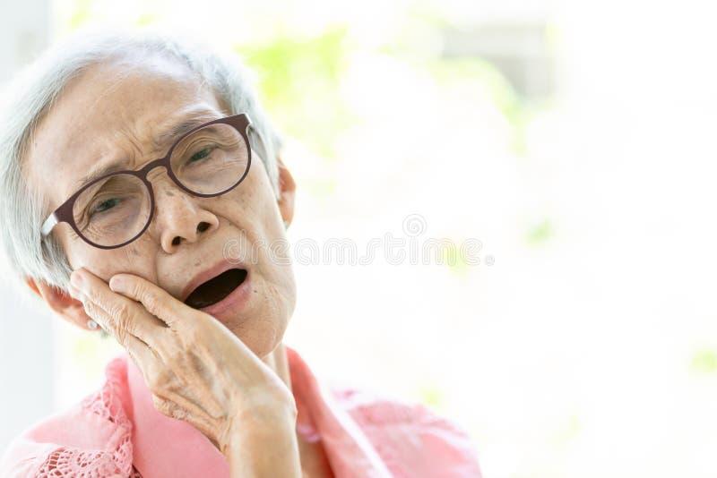 Den asiatiska höga kvinnan som lider från tandvärk, tandförfall, känsla smärtar, kvinnligt äldre folk som rymmer hennes kind med  fotografering för bildbyråer