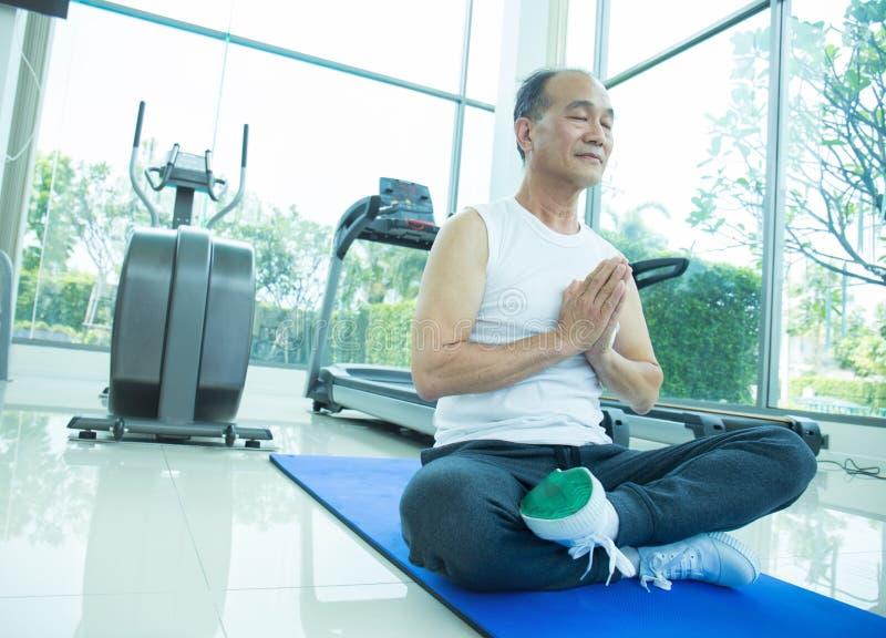 Den asiatiska höga mannen som gör yoga, den gamla asiatiska mannen, satte hans händer som gör tillsammans meditation arkivbilder