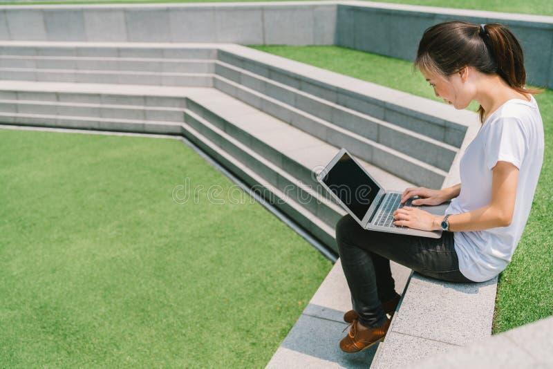 Den asiatiska högskolestudenten eller frilanskvinnan som använder bärbara datorn på trappan i universitetsområde, eller offentlig fotografering för bildbyråer