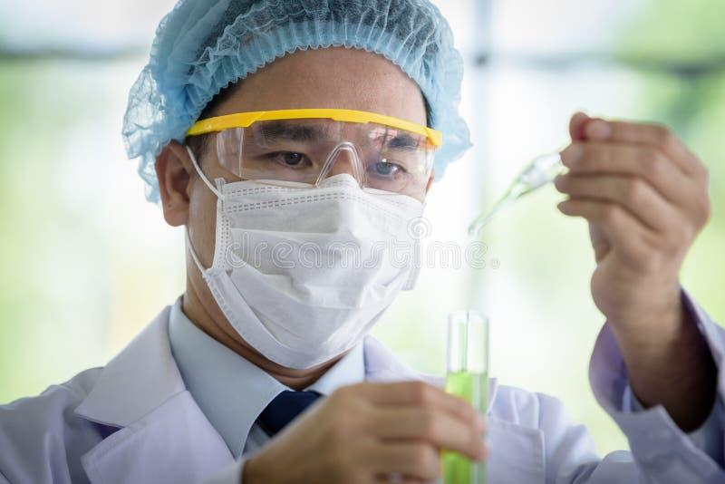 Den asiatiska h?ga forskaren har den undervisande unga studentforskaren i ett laboratorium fotografering för bildbyråer