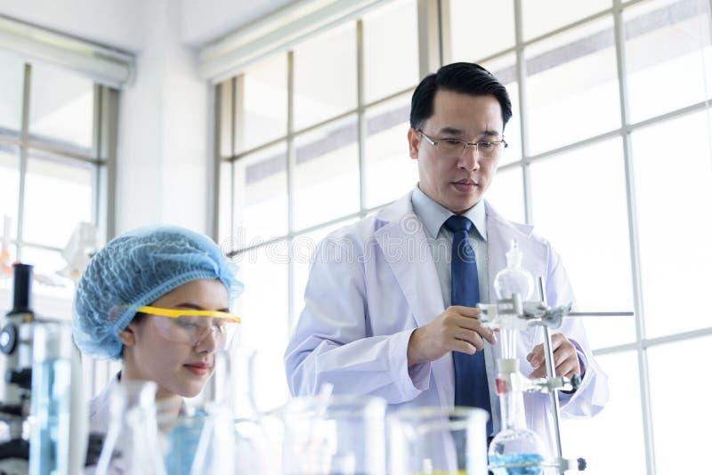 Den asiatiska h?ga forskaren har den undervisande unga studentforskaren i ett laboratorium royaltyfri foto