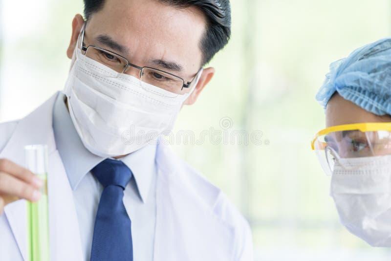 Den asiatiska h?ga forskaren har den undervisande unga studentforskaren i ett laboratorium arkivfoton
