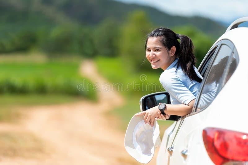 Den asiatiska handelsresanden och turism för ung kvinna går till turer reser på halvkombibilen till destinationen och fritidlopp  arkivbild