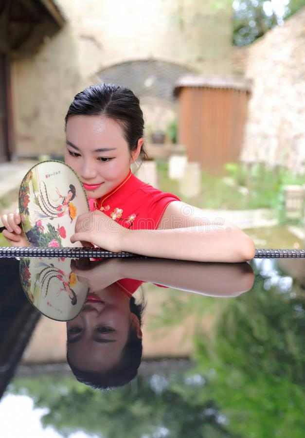 Den asiatiska kinesiska chi-paocheongsamkvinnan med den klassiska broderade fanen tycker om avkopplad fri tid i inverterad reflex royaltyfri foto