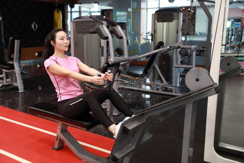 Den asiatiska kinesiska kvinnan i den ŒFitness för idrottshallï¼ som kvinnan gör triceps, övar i idrottshallen Attraktivt vuxen m arkivfoton