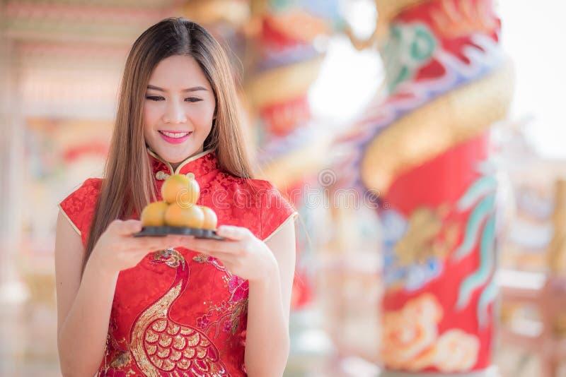 Den asiatiska kinesiska kvinnan i hållande apelsinPA för traditionell kines fotografering för bildbyråer