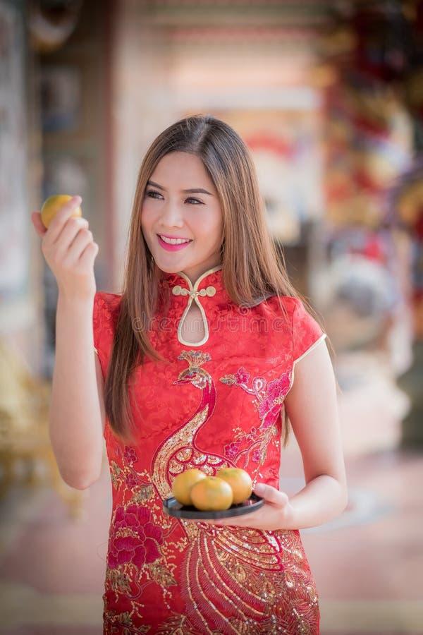 Den asiatiska kinesiska kvinnan i hållande apelsinPA för traditionell kines arkivbilder