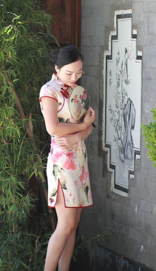 Den asiatiska kinesiska kvinnan i traditionell cheongsam tycker om fri tid royaltyfri foto