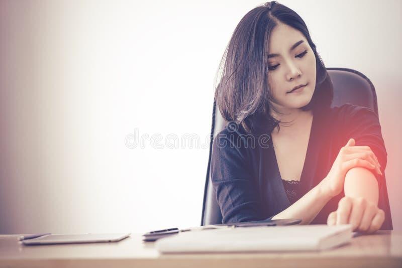 Den asiatiska kontorsarbetaren lider från skada för kontorssyndromtrötthet på hennes arm arkivbild