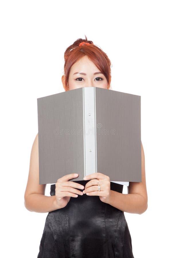 Den asiatiska kontorsflickan är blyg och stänger hennes lägre framsida med en mapp royaltyfria foton