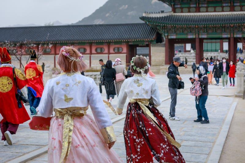 Den asiatiska koreanska kvinnan klädde Hanbok i traditionell klänning som går i den Gyeongbokgung slotten royaltyfri foto