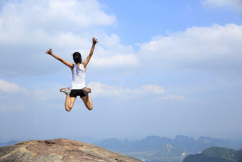 Den asiatiska kvinnabanhoppningen på bergmaximum vaggar arkivbild