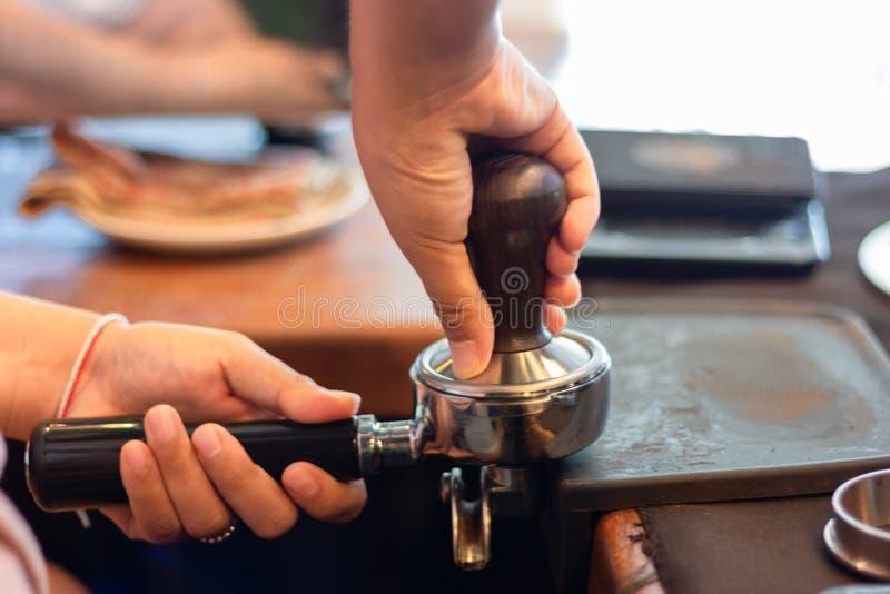 Den asiatiska kvinnabaristaen trycker på att använda för jordkaffe fifflar in i portafilter, slut upp händer arkivfoton