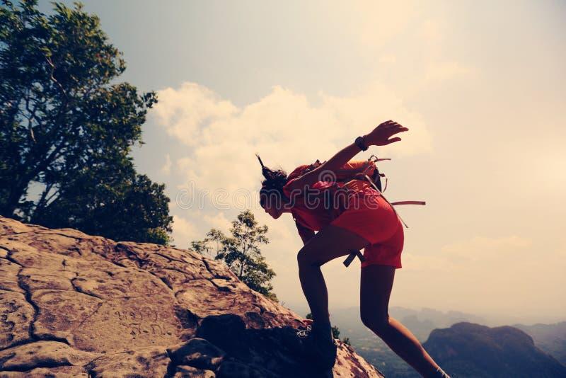 Den asiatiska kvinnafotvandrareklättringen vaggar på klippan för bergmaximumet fotografering för bildbyråer