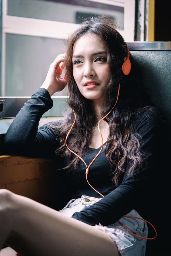Den asiatiska kvinnahandelsresanden har lyssnande musik med telefonen och den orange headphonen inom drevet på den Hua Lamphong s fotografering för bildbyråer