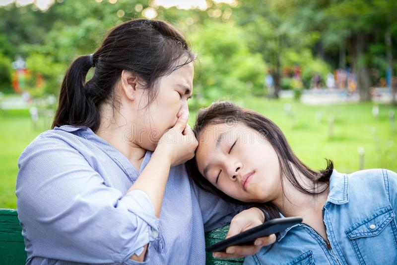 Den asiatiska kvinnan är missnöjd med lukten av hennes dotters hår, dålig lukt, en flicka tar en tupplur nära sin mor, mamma royaltyfria bilder