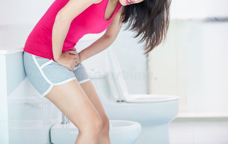 Den asiatiska kvinnan önskar att urinera royaltyfria bilder