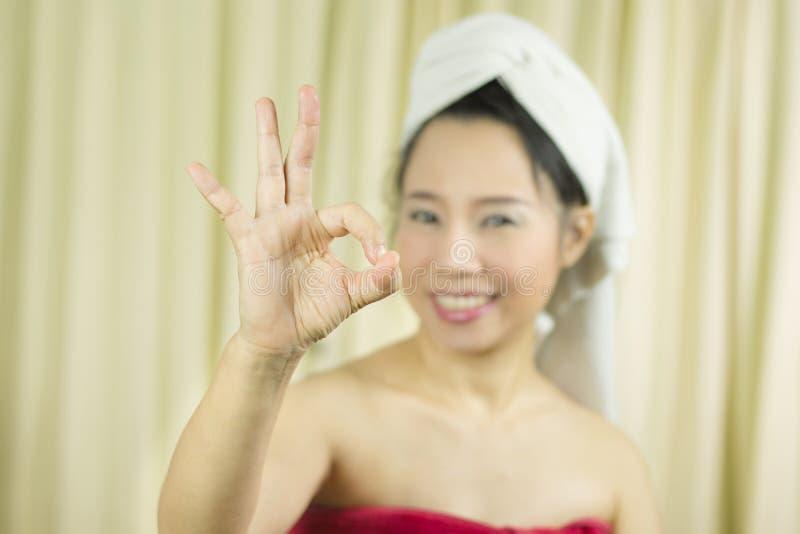 Den asiatiska kvinnan b?r en kjol f?r att t?cka hennes br?st efter tv?ttar h?r som sl?s in i handdukar, n?r dusch och han har giv arkivfoton