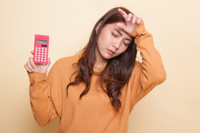 Den asiatiska kvinnan fick huvudvärk med räknemaskinen royaltyfri fotografi