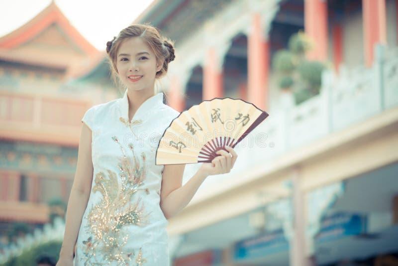 Den asiatiska kvinnan framgångar i för kinesisk klänning för den hållande rimmat verspar '(haka fotografering för bildbyråer