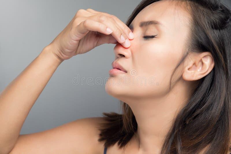 Den asiatiska kvinnan gör ont hennes näsa, därför att hon har förkylning arkivbild