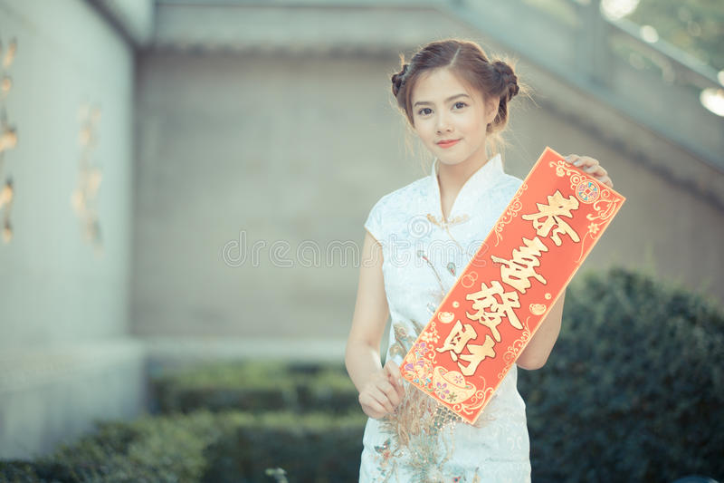 Den asiatiska kvinnan i 'den inbringande' hållande rimmat verspar för kinesisk klänning (C royaltyfri fotografi