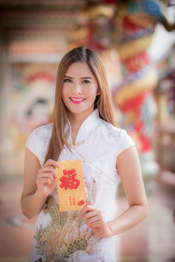 Den asiatiska kvinnan i 'den lyckliga' hållande rimmat verspar för kinesisk klänning (bergskammen royaltyfri foto