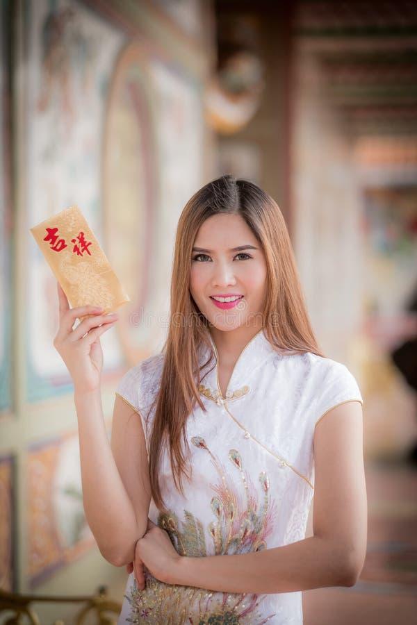 Den asiatiska kvinnan i 'den lyckliga' hållande rimmat verspar för kinesisk klänning (bergskammen royaltyfri fotografi