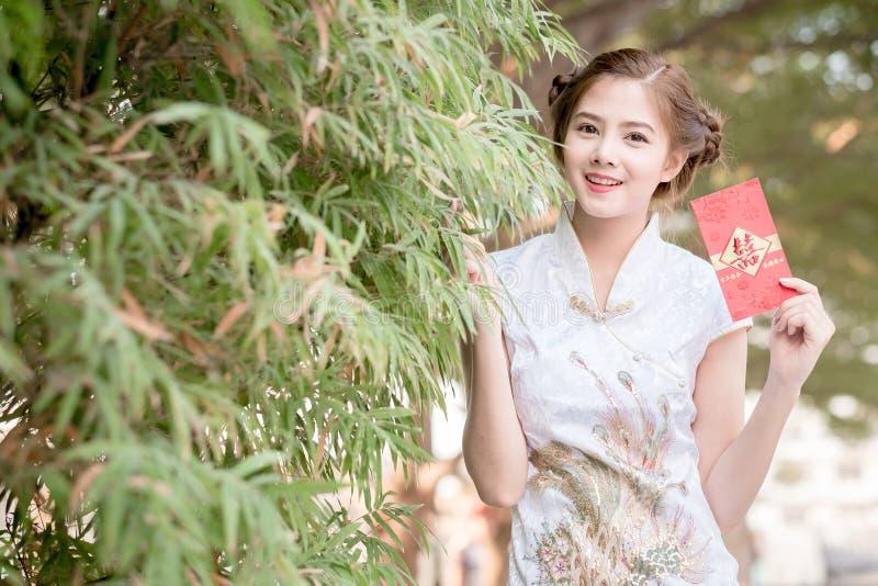Den asiatiska kvinnan i 'den lyckliga' hållande rimmat verspar för kinesisk klänning (bergskammen royaltyfria foton
