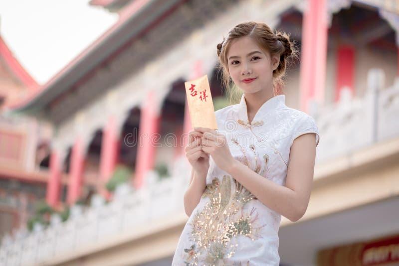 Den asiatiska kvinnan i 'den lyckliga' hållande rimmat verspar för kinesisk klänning (bergskammen arkivbilder