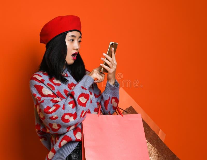 Den asiatiska kvinnan i en stilfull basker och tröja, med en färgrik shoppa påse ser in i hennes mobiltelefon, och något för royaltyfri fotografi