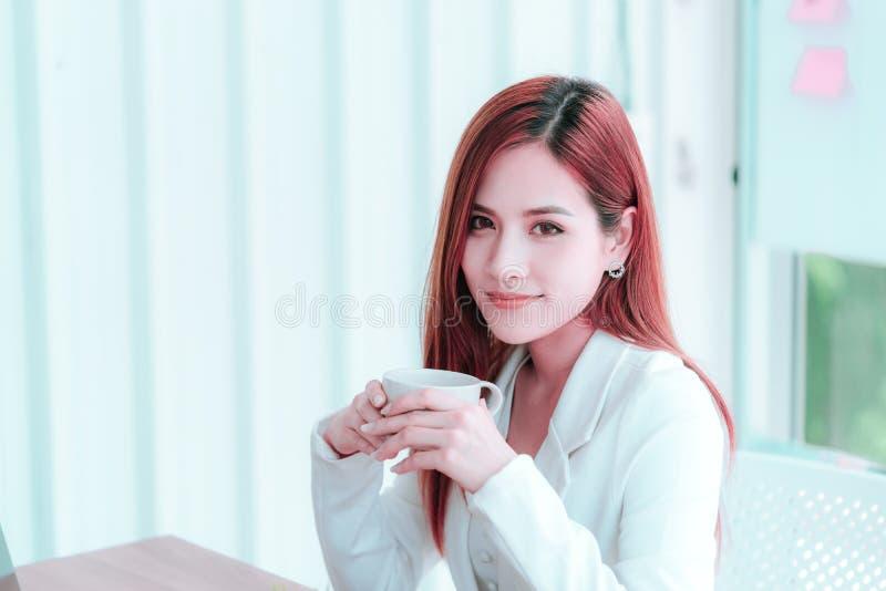 Den asiatiska kvinnan i vit tar ett avbrott med varmt kaffe arkivfoto