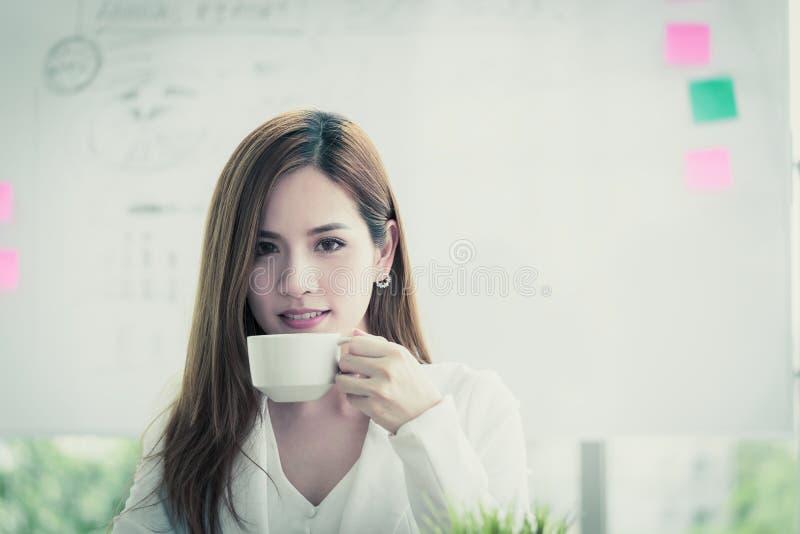 Den asiatiska kvinnan i vit tar ett avbrott med varmt kaffe arkivbilder