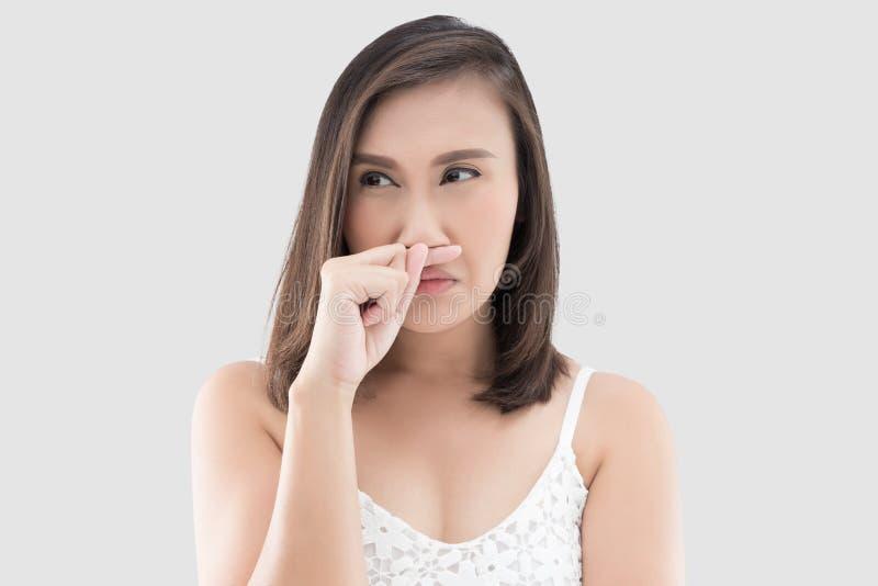 Den asiatiska kvinnan i den vita klänningen fångar hennes näsa på grund av en dålig lukt arkivbild