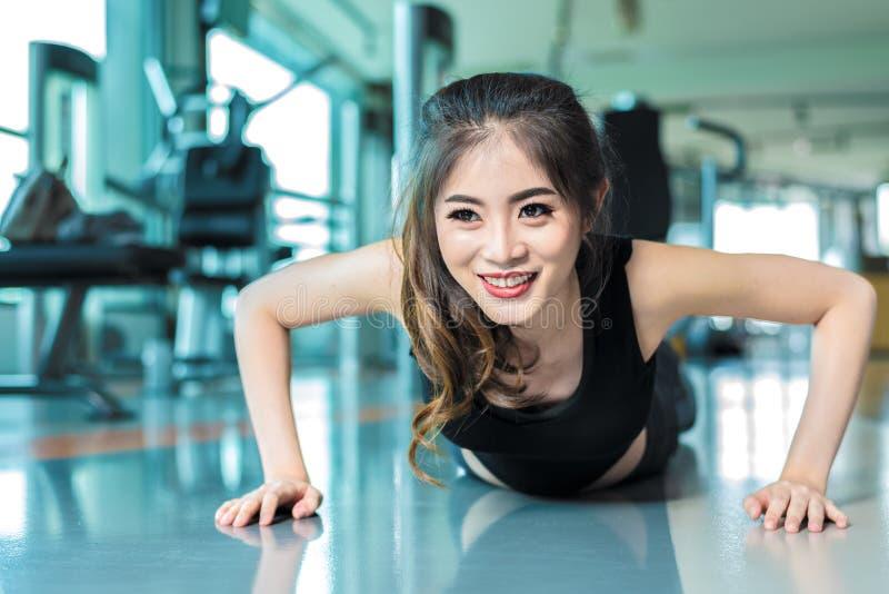 Den asiatiska kvinnan kondition somflickan gör driftigt, ups på konditionidrottshallen Healthca royaltyfria foton