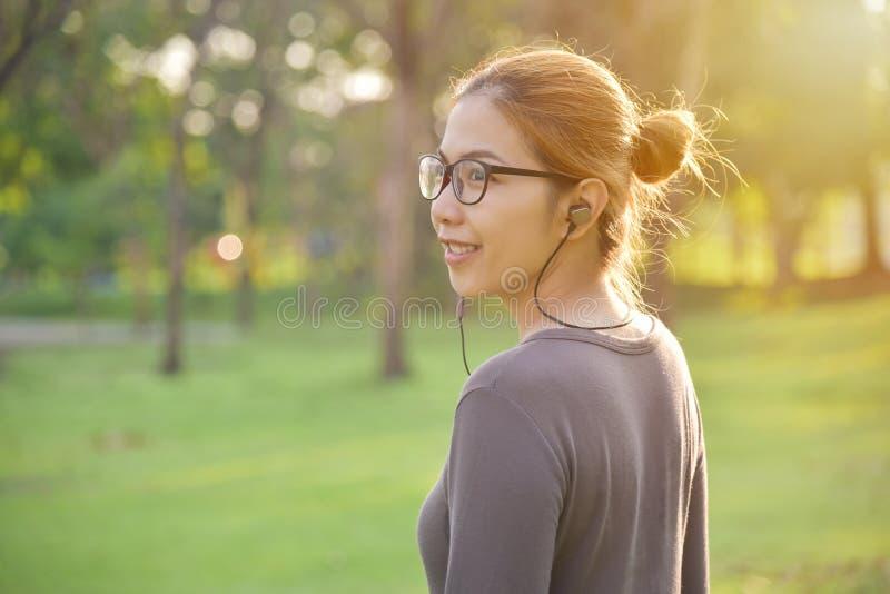 Den asiatiska kvinnan lyssnar till musiken arkivbild